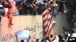 محتجون مصريون يمزقون علم الولايات المتحدة أمام جدار للسفارة الأميركية في القاهرة العام الماضي