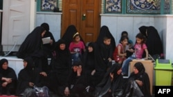 Women and children sit at the shrine of Imam Mussa al-Kadhim in the district of Kadhimiya.