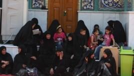 Women and children sit at the shrine of Imam Mussa al-Kadhim in the district of Kadhimiya.