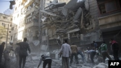 Syria -- Syrian civilians and rescuers gather at site of government forces air strikes in the rebel held neighbourhood of Al-Shaar in Aleppo on September 27, 2016.