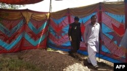 Pakistani police beside the grave of Sana Cheema before her exhumation on April 25