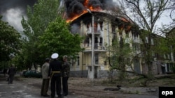Люди смотрят на охваченное огнем здание милиции. Мариуполь, 9 мая 2014 года.