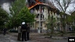 Өртеніп жатқан милиция ғимараты қасында тұрған адамдар. Мариуполь, Укрина, 9 мамыр 2014 жыл.