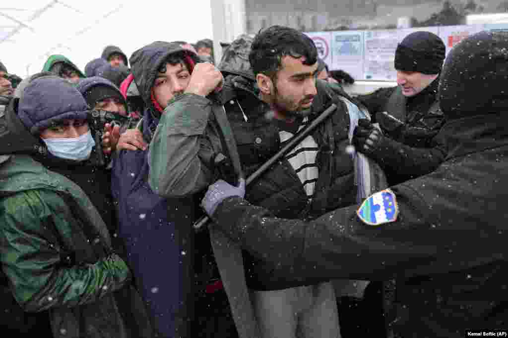 A policeman pushes migrants as they wait to be relocated at the Lipa camp on December 26. The camp was to be closed on December 23 and relocated. However, officials said the move had to be postponed since the camp was almost entirely destroyed in the fire. Bosnia has become a bottleneck for thousands of migrants hoping to reach neighboring European Union member Croatia and then head toward other Western EU members.