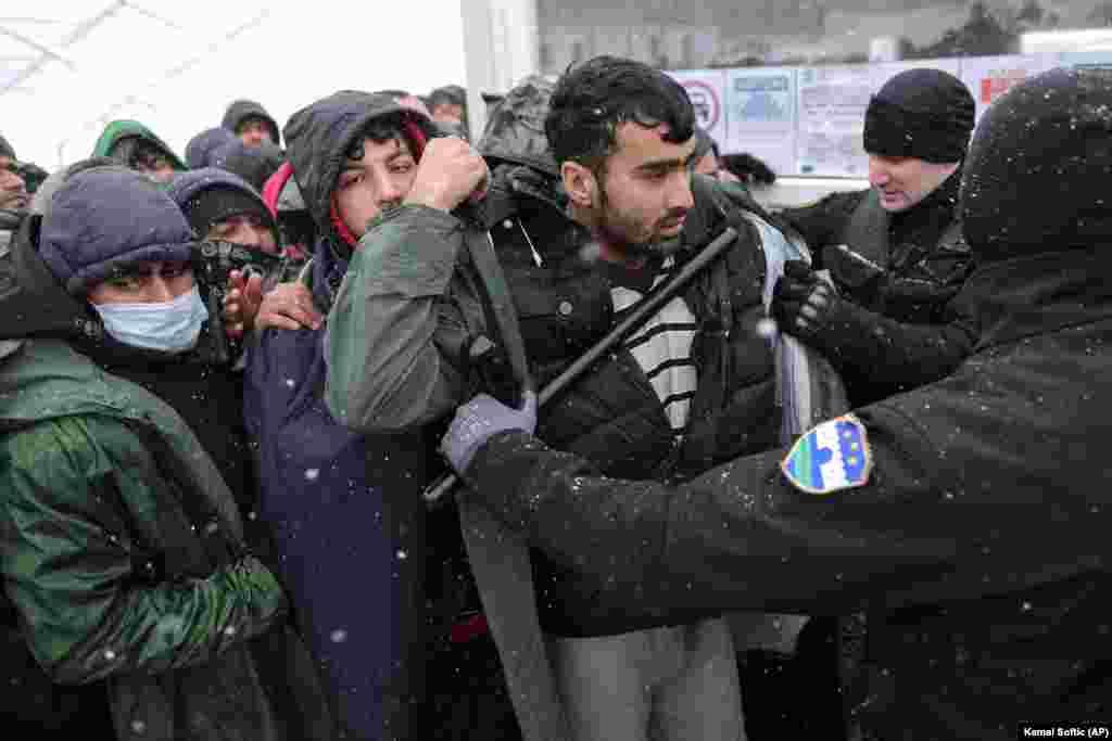 Un polițist față în față cu refugiații care așteaptă să fie mutați în tabăra de la Lipa pe 26 decembrie. Tabăra urma să fie închisă pe 23 decembrie și relocată. Cu toate acestea, oficialii au spus că operațiunea trebuie amânată, deși tabăra a fost distrusă aproape în totalitate în urma incendiului. Bosnia a devenit o piedică în calea miilor de migranți. Aceștia speră să ajungă în Croația vecină care este membră a Uniunii Europene și, de acolo, să se îndrepte către alte țări-membre ale UE occidentale.