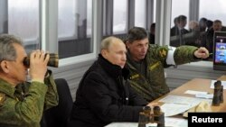 Russian President Vladimir Putin (enter), Defense Minister Sergei Shoigu (left), and the head of the Russian Army's main department of combat preparation, Ivan Buvaltsev, watch military exercises in the Leningrad region earlier this month.