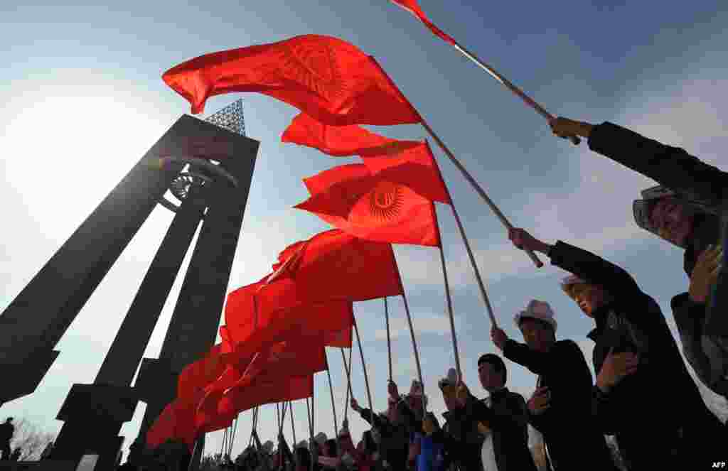 Kyrgyz men wearing traditional hats hold national flags during a rally marking National Flag Day in Bishkek on March 3. (AFP/Vyacheslav Oseledko)