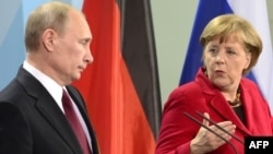 German Chancellor Angela Merkel speaks next to Russian President Vladimir Putin during a press conference in Berlin