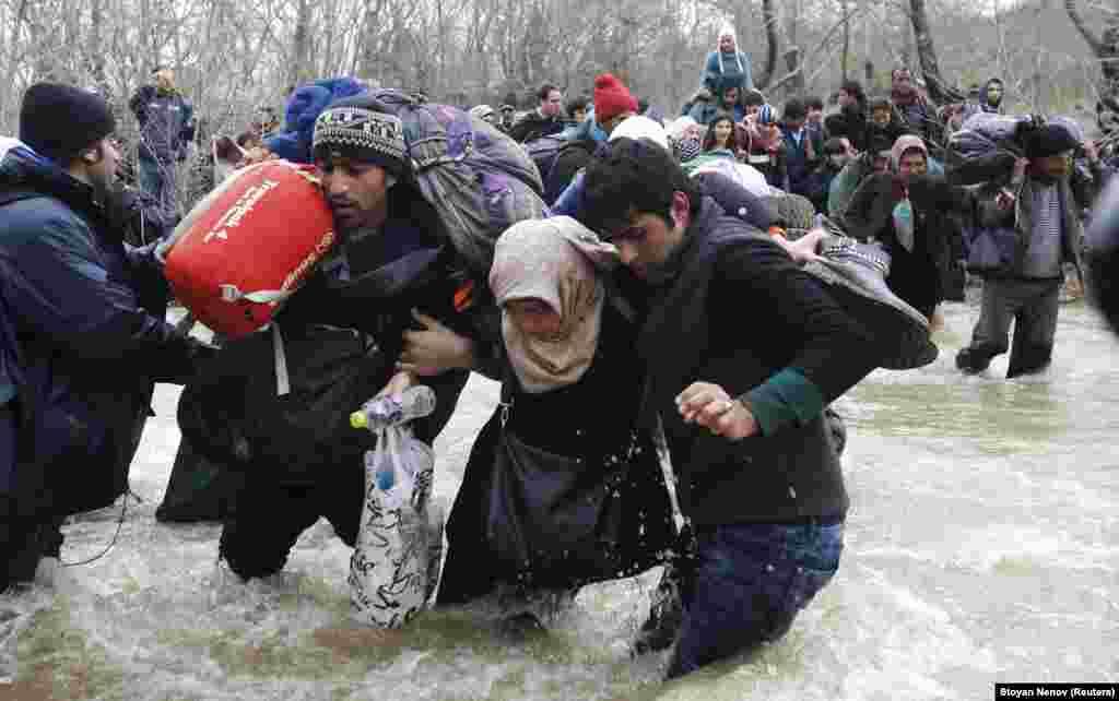 Migrants wade across a river near the Greek-Macedonian border, west of the village of Idomeni, Greece. (Reuters/Stoyan Nenov)