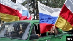 People wave Russian and South Ossetian flags in Tskhinvali, the South Ossetia capital, after Russia recognized the region as independent.