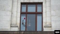 Muškarac stavlja cveće u prozor zgrade Doma sindikata u Odesi
