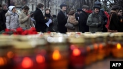 People wait for their turn to lay flowers and place candles at a memorial to the victims of Soviet-era political repression on Lubyanka Square in Moscow.