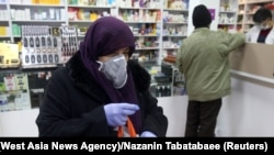 Iran -- An Iranian woman wears a protective mask at a drug store in Tehran, February 25, 2020.