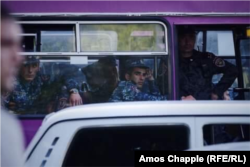 Police look on from their bus as their colleagues attempt to clear the top of Yerevan's Mashtots avenue of parked cars and protesters on April 25.