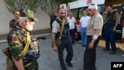 Armenia -- A picture taken on July 17 and made available on July 19 shows armed men standing by an ambulance car at the yard of Erebuni police station in Yerevan seized by them.