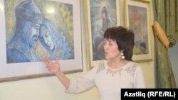 """Рәссам Ольга Бакиева """"Күчем һәм Сүзге"""" рәсеме янында"""