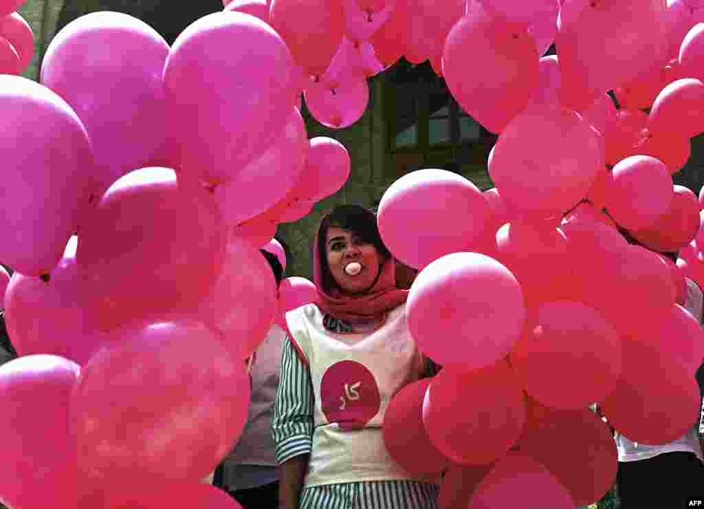 """An Afghan volunteer blows a chewing-gum bubble as she prepares balloons for the """"We Believe in Ballons"""" event, an art project promoting peace in Kabul on May 25. (AFP/Massoud Hossaini)"""