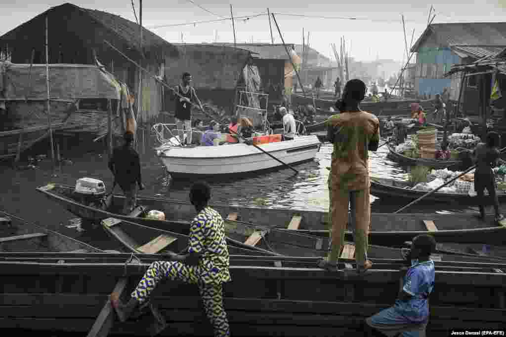 A boat with tourists from Lagos Marina is steered through the canals of the Makoko community -- an ancient fishing village that has grown into an enormous informal settlement on the shores of Lagos Lagoon in Nigeria. Contemporary Issues -- First Prize, Singles (Jesco Denzel)