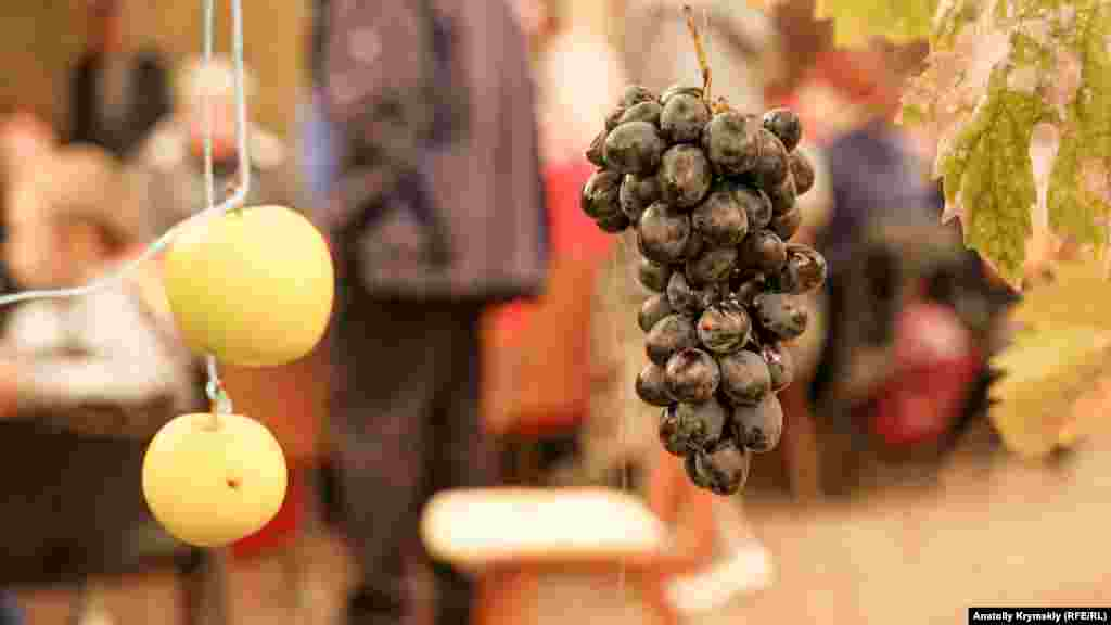 Во дворе развесили гроздья столового винограда, яблоки, гранат и конфеты