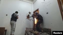 Dy pjesëtarë të Ushtrisë së Lirë të Sirisë i mbajnë pozicionet mbrojtëse në një shtëpi