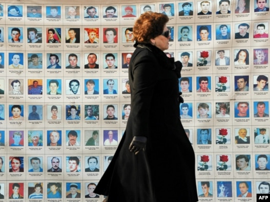 An woman walks past a wall in Pristina on January 25 of photos depicting people missing since the 1998-99 conflict in Kosovo.