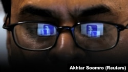 FILE: Facebook logo is reflected in the glasses of a Pakistani user.