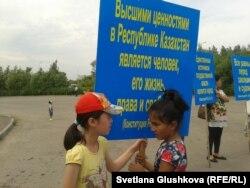 Девочки на акции протеста против изъятия земель под государственные нужды держат плакат с цитатой из Конституции Казахстана. Астана, 28 июня 2014 года.