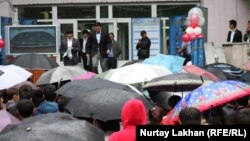 Выпускники выходят после сдачи ЕНТ на улицу, где их ждут родители и учителя. Алматы, июнь 2013 года.