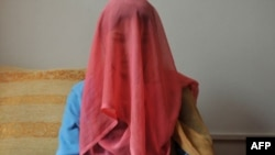 "A veiled Kyrgyz bride sits for a photograph. Up to three-quarters of contemporary Kyrgyz brides are betrothed through ""bride kidnapping"" rituals. Now the Kyrgyz parliament is considering legislation that may chip away at the practice."