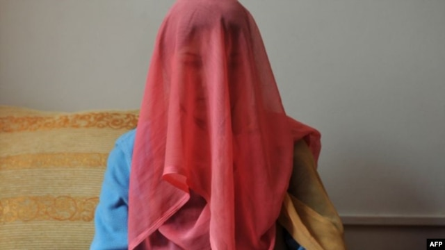 """A veiled Kyrgyz bride sits for a photograph. Up to three-quarters of contemporary Kyrgyz brides are betrothed through """"bride kidnapping"""" rituals. Now the Kyrgyz parliament is considering legislation that may chip away at the practice."""