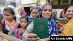 A Hindu refugee who migrated from Pakistan's Sindh Province of Pakistan shows her passport in India. (file photo)