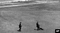 Пограничники забирают с полосы отчуждения человека, который пытался бежать и был ранен пулеметным огнем. 1971 год.
