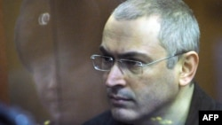 Former Yukos chief Mikhail Khodorkovsky stands behind a glass wall in a courtroom in Moscow during a hearing in 2010.