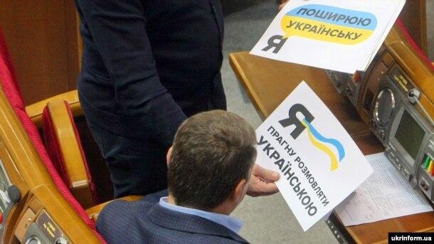 Народний депутат Іван Крулько у Верховній Раді демонструє колезі листівку з написом «Я прагну розмовляти українською». Київ, 4 листопада 2016 року