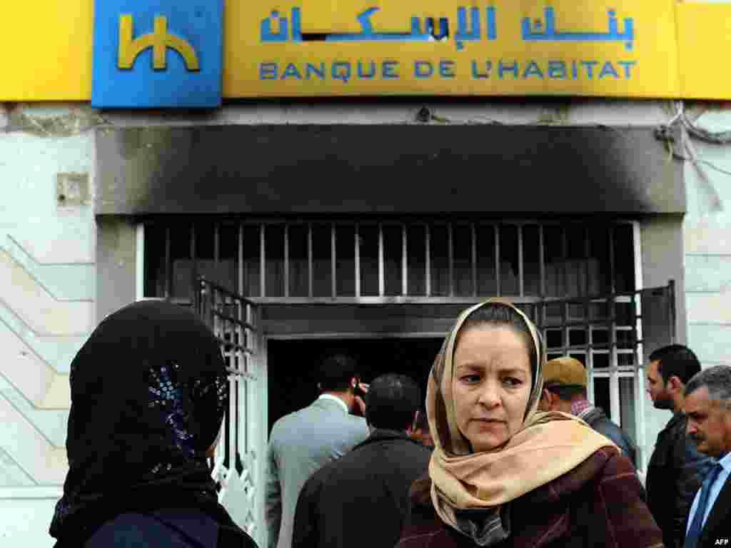 تجمع مردم بیرون از یک بانک در شهر تونس که در جریان اعتراضها به آتش کشیده شده است.