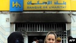 Люди у входа в подожженное здание банка в Тунисе
