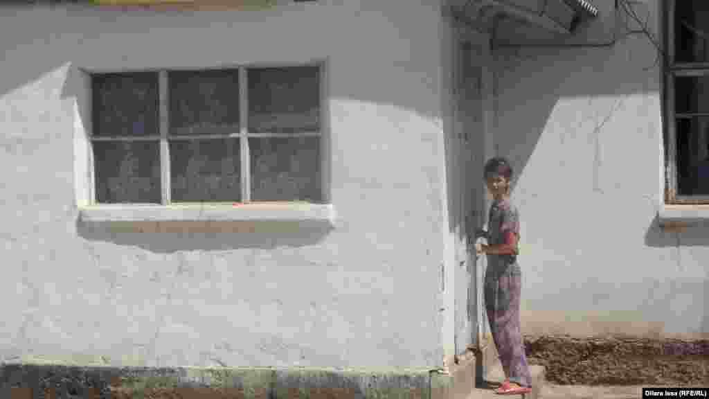 Внучка Айбоби запирает дверь дома, в котором семья прожила пять лет. По словам женщины, средств для оплаты аренды дома у них больше не было.