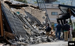 Residents walk through debris and observe the damage in the town of Mashiki, where an earthquake hit on April 15.