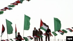Young Hamas supporters are surrounded by Hamas and Palestinian flags as they put the last touches on preparations for today's celebrations.