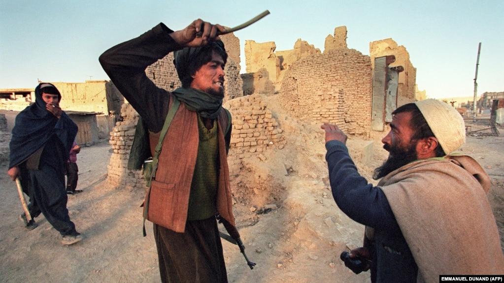 A Taliban militant attacks a civilian in Kabul in 1996. (file photo)
