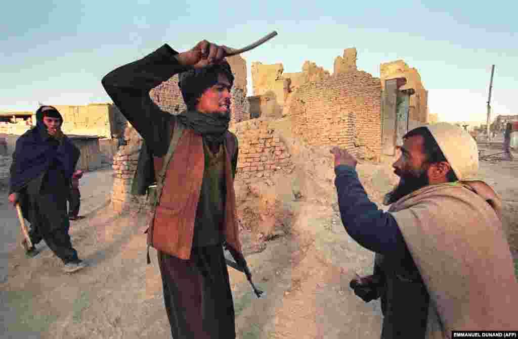 Un taliban lovește un bărbat prins cu jumătate de kilogram de opiu. Grupul sunnit a promis că va restabili ordinea și va eradica corupția în Afganistanul devastat de război.