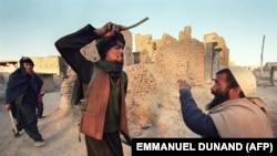 آرشیف، یک جنگجوی طالبان یک مرد را دره میزند. November 6, 1996