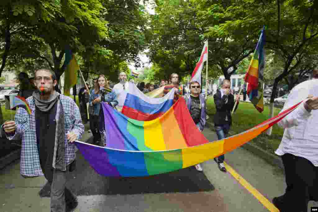 Members of the LGBT community carry a rainbow-colored flag as they attend a march for human rights and equality in Chisinau, Moldova, on May 17. (epa/Dumitru Doru)