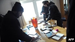 Some of those who stormed an office at the British Embassy in Tehran look through documents and other belongings on November 29.