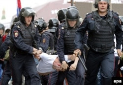 Riot police detain a man during the protest on Tverskaya Street in central Moscow on June 12.