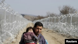 A migrant from Afghanistan holding a child walks next to a border fence at the Macedonian-Greek border in Gevgelija.