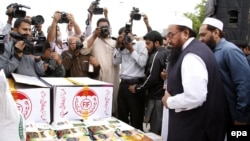 Hafiz Saeed (2-R), head of banned Islamic charity Jamat-ud-Dawa that now works with a new name Falah-e-Insaniyat Foundation, dispatch relief goods and cash funds for the victims of earthquake, at their relief good collection center in Islamabad on November 2.