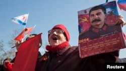 Женщина держит календарь с фотографией Сталина во время трансляции выступления президента России Владимира Путина в центре Севастополя. 18 марта 2014 года.