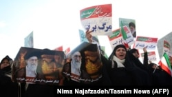 Iranian pro-government supporters hold posters of Supreme Leader Ayatollah Ali Khamenei during a rally in support of the regime in the city of Mashhad on January 4.