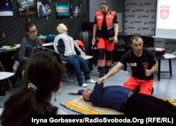 Спасатель Мальтийской службы показывает приемы транспортировки пострадавшего